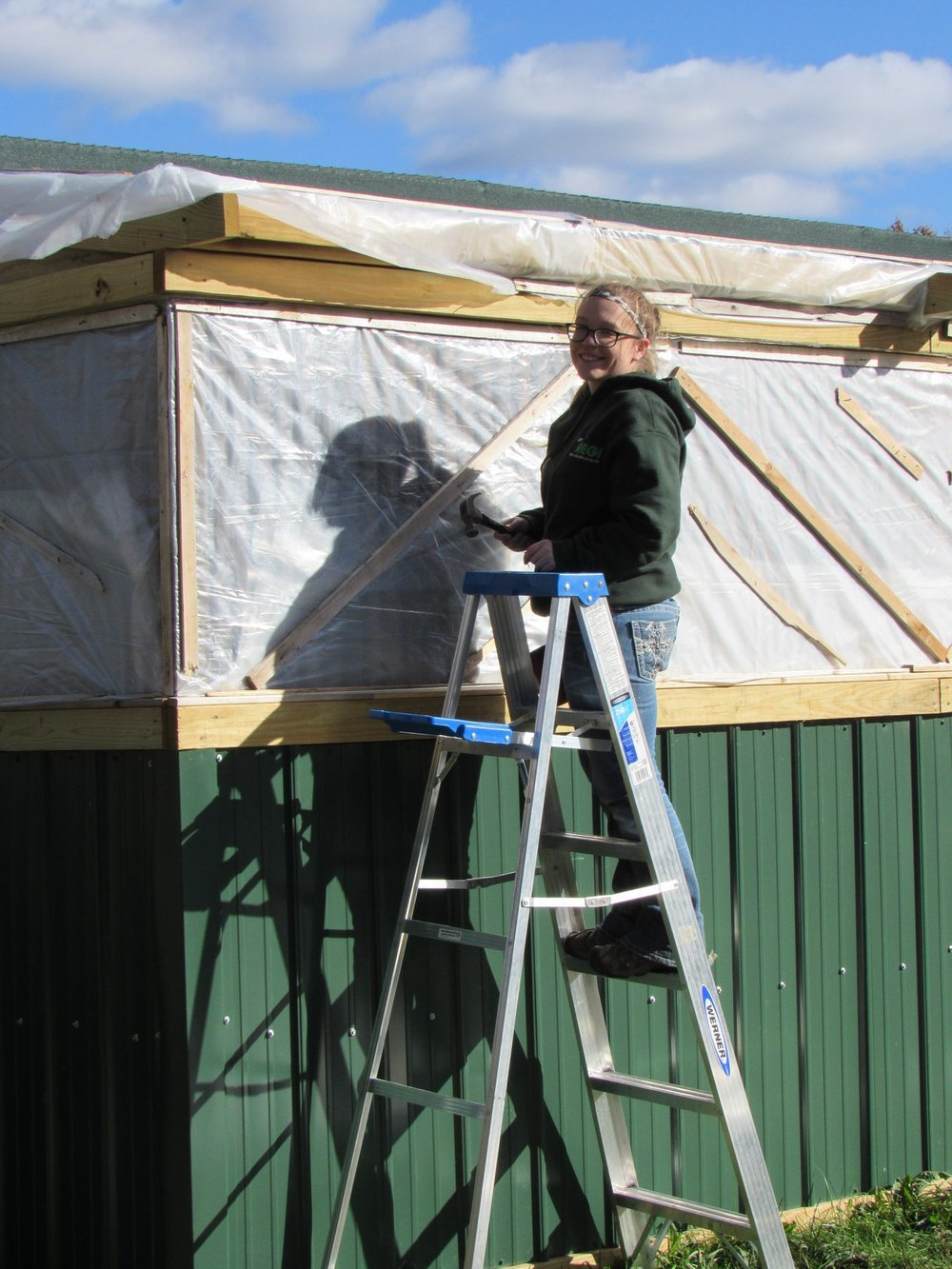Intern Sarah pounding nails to winterize a new enclosure.