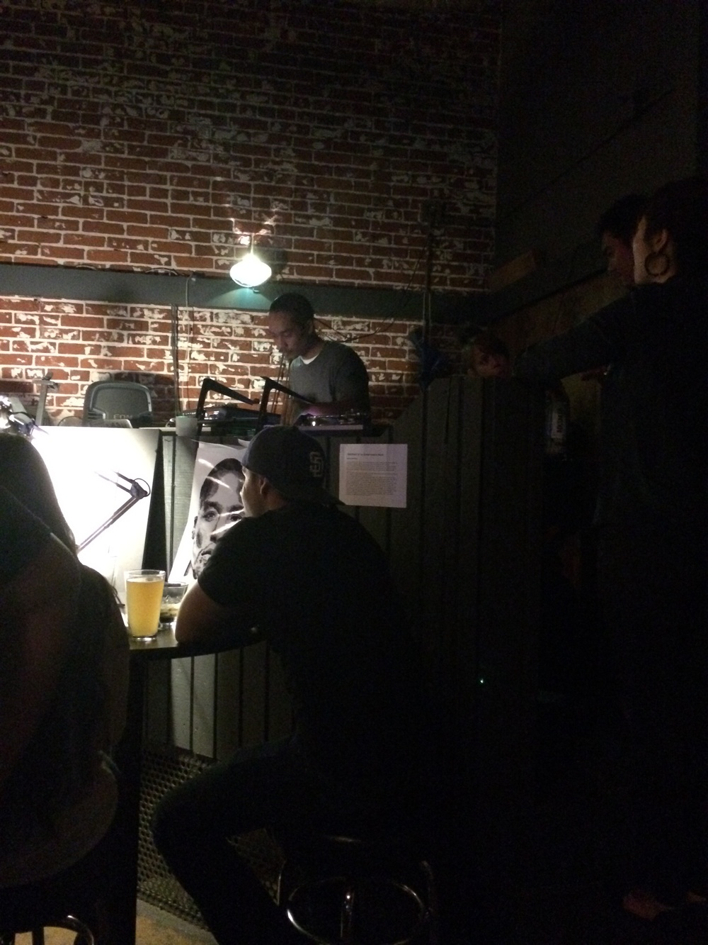 The DJ is spinning dope hip hop just above a lady creating a picture of Tupac Shakur.