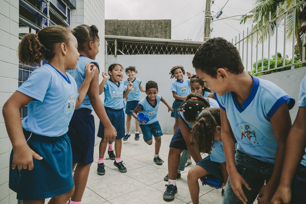 Emidio comes alive during action games and is very competitive. On this day, Emidio and his friends play a game where they must pass a cup between their legs to the person behind them and then run up to the front of the line. The goal is to have their group finish a whole cycle first.