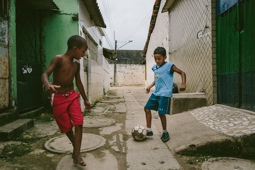 "On the way home, Emidio's friend spots him and asks if he wants to pass the ball around while he walks home. Soccer is the most popular sport in Brazil and home to the 2014 World Cup. After his time at the Compassion Center, Emidio walks to his ""aunt's"" house (family friend---no relation) to be taken care of before heading to school since his mother works until 10pm each night."