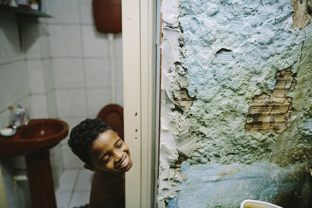 "Ever the playful boy, even bathtime is a chance for Emidio to joke around. Each day an ""aunt"" (family friend--relation) takes care of Emidio and his younger brother between his time at the Compassion Center and School since his mother works until 10pm at night."