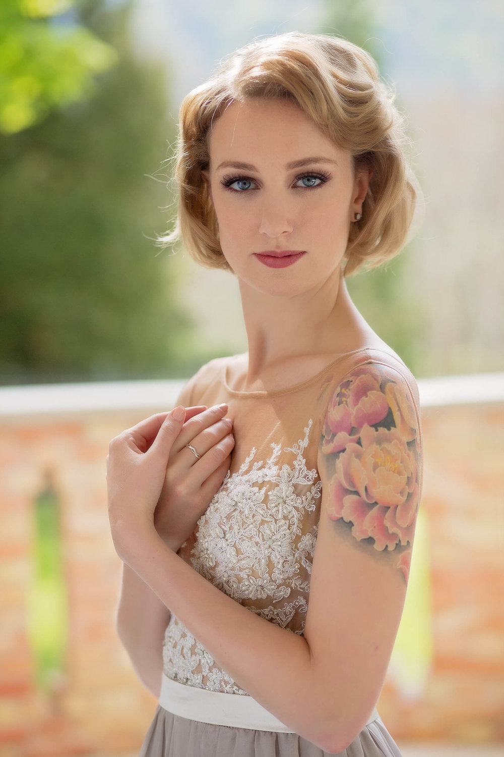 Beautiful backlit portrait of women with tatto in elegant gown