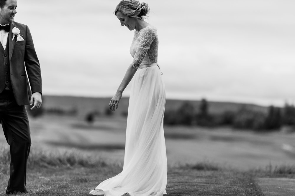 black and white wedding image on a hill. Bride is dancing while groom watches her dance.