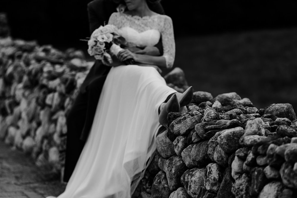 Modern bride holding her flower while leaning against her husband while sitting on a wall of rocks.