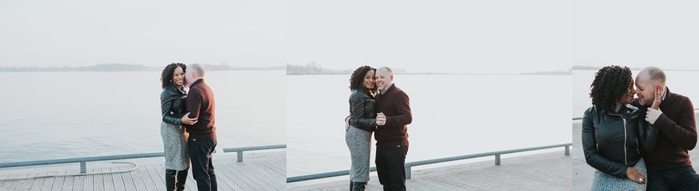 a couple cuddle on a pier in Toronto waterfront area