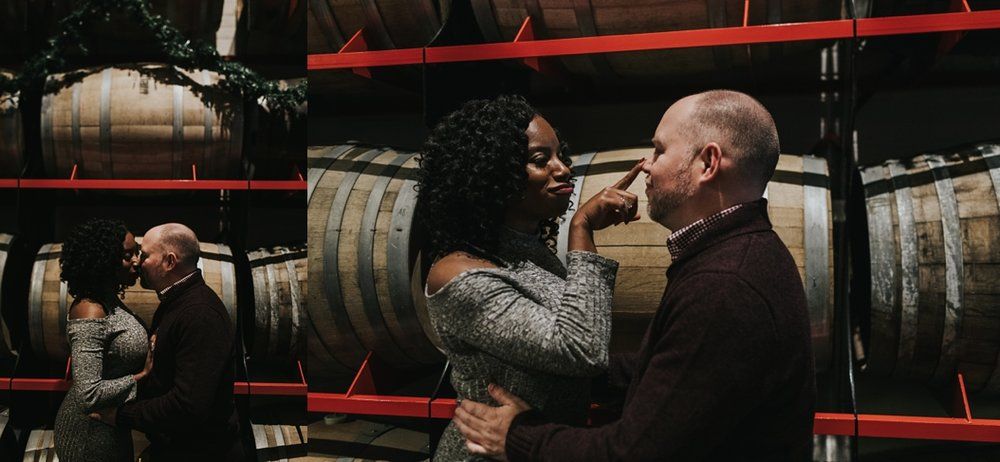 couple in front of wine barrel inside a wine store. couple kissing