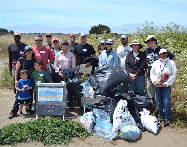 Volunteers proudly display all the trash picked up after a workday.