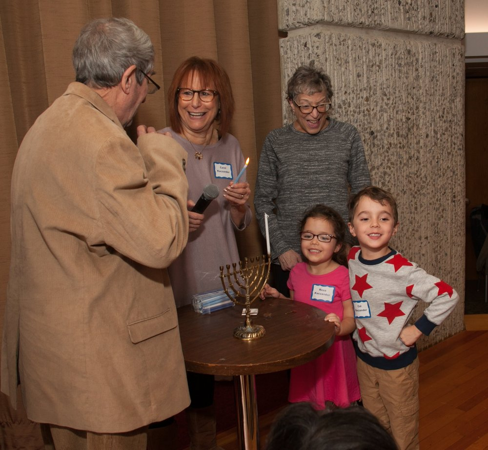 JARC Staff and family member Carol Kaczander and grandchildren Rosa and Calvin Kaczander lighting the Menorah at the annual Hanukkah Party with Jack Resnick and Marsha Kowal.