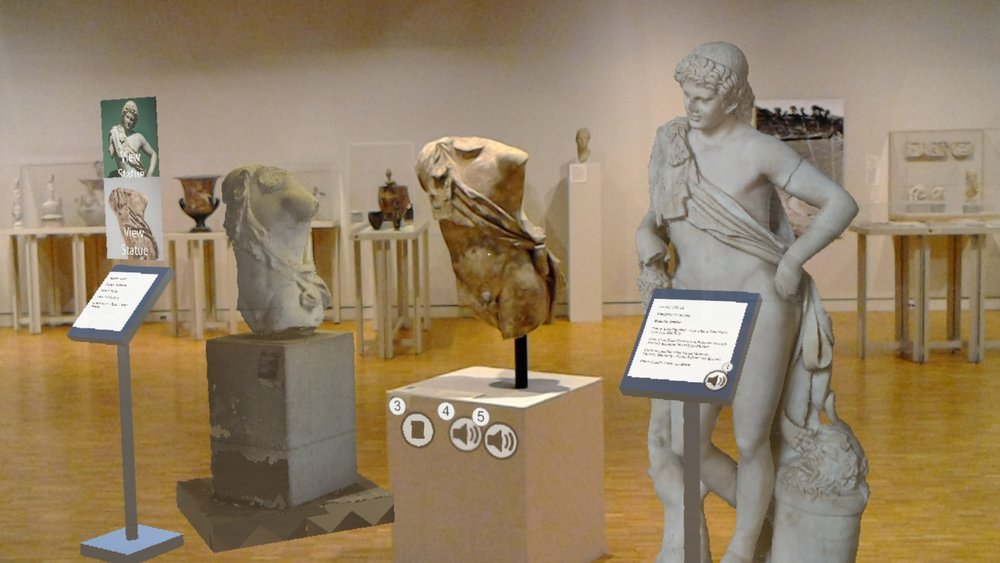 A view through the HoloLens of the final design in the museum. The center statue is physically in the space, while the others are virtual models.