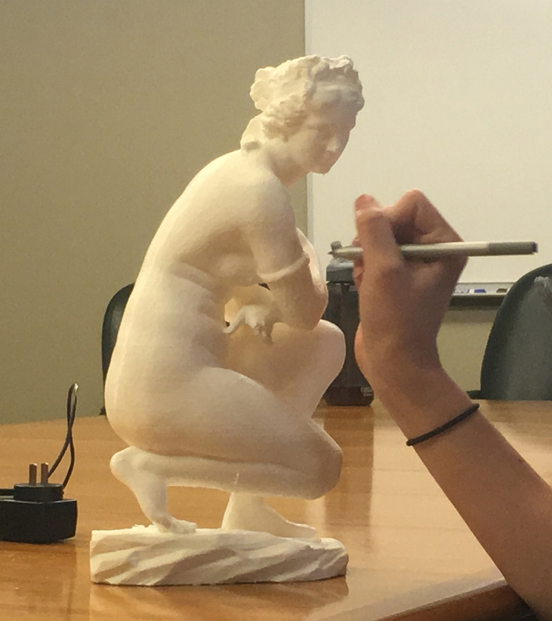 An image of the Crouching Aphrodite during a test, a user is attempting to take a note with the provided pen.