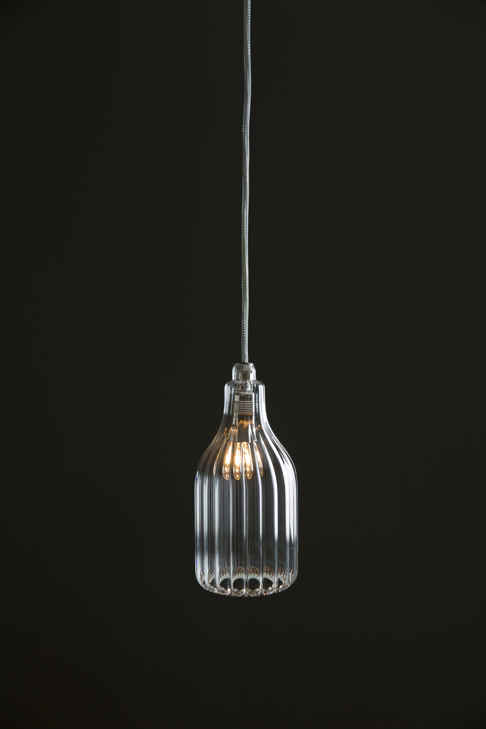 POTUM LUX PENDANT: Vertical Description:  Hand blown vertical glass pendant in conturax glass. Materials:  Conturax borrow ciliate glass, chrome E14 lamp holder, chrome ceiling rose, silver flex cable.  Dimensions: In either  47mm x 140mm, 52mm x 140mm or 60mm x 140mm