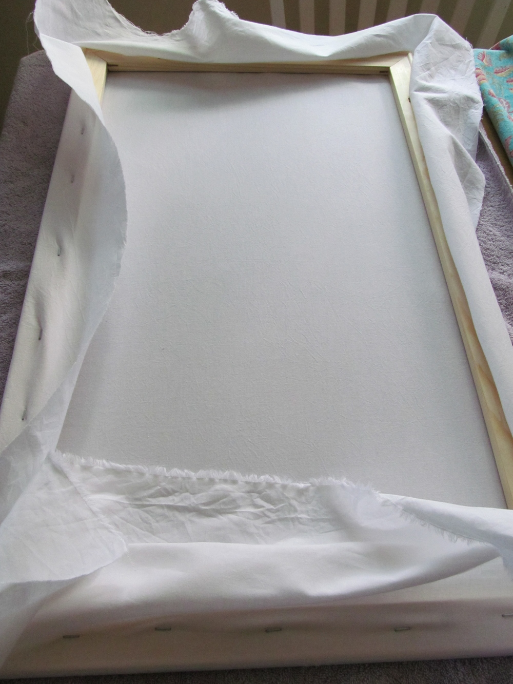 First, I stretch white muslin over the wooden stretcher bars.