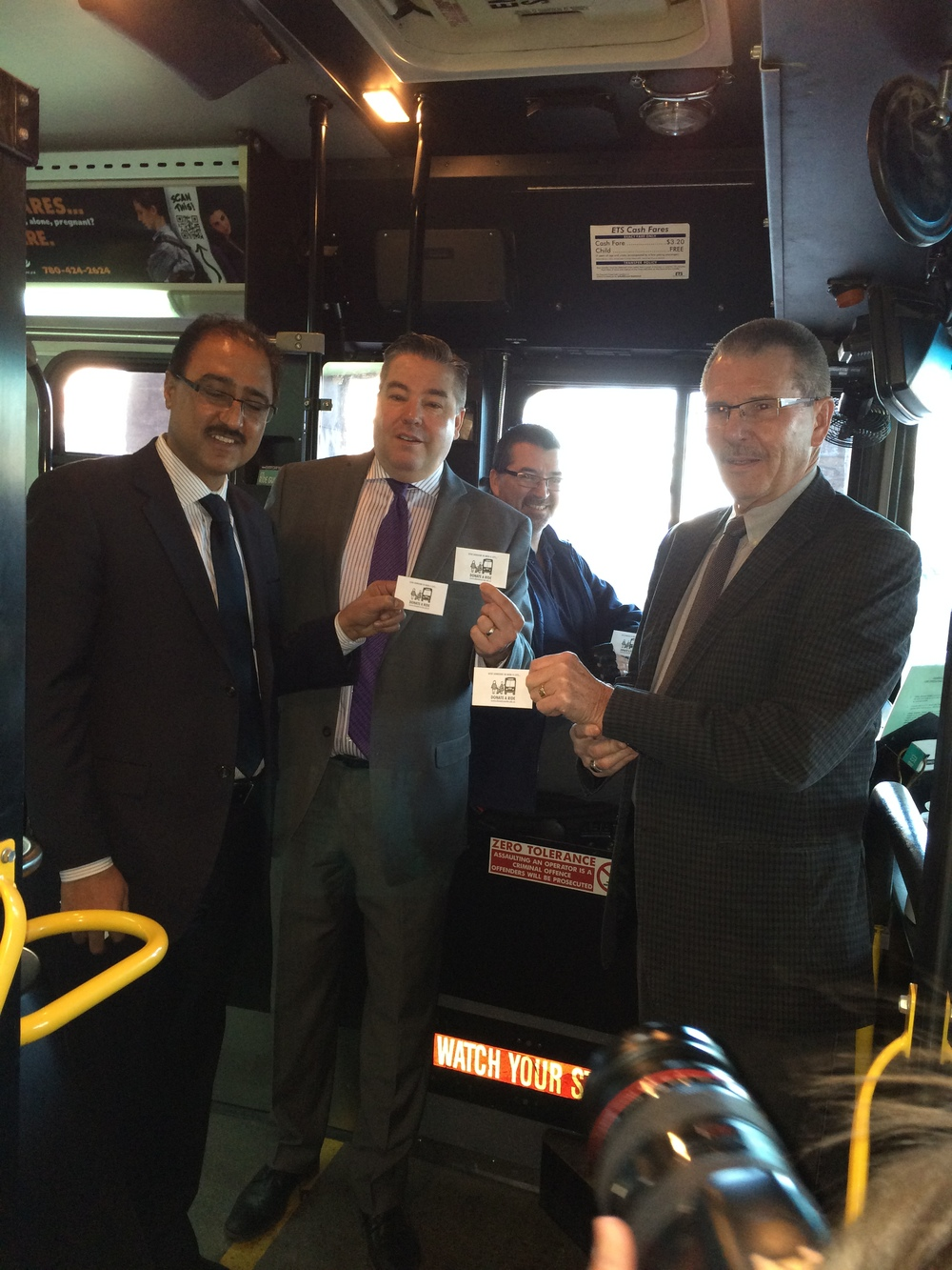 Councillors Anderson, Loken, and Sohi hop aboard an ETS bus to make a ticket donation for Donate-A-Ride.
