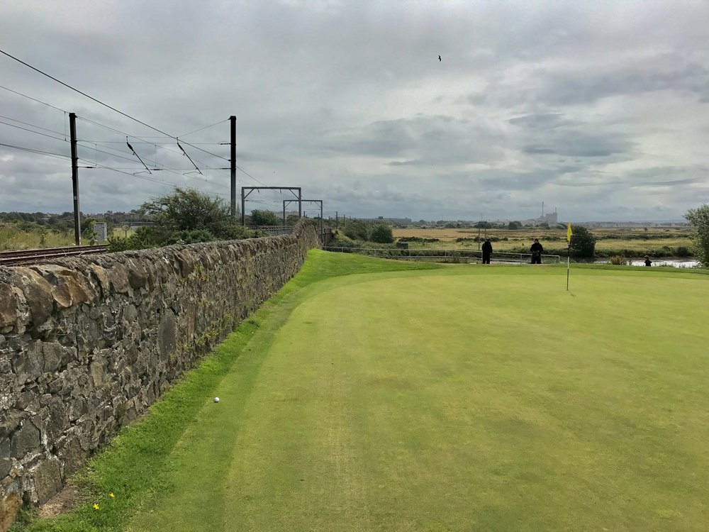 Bank shot, left handed, or way behind stance?  The 4th green at Bogside gets closer to the railway wall than any other hole (that I know of) in Ayrshire.