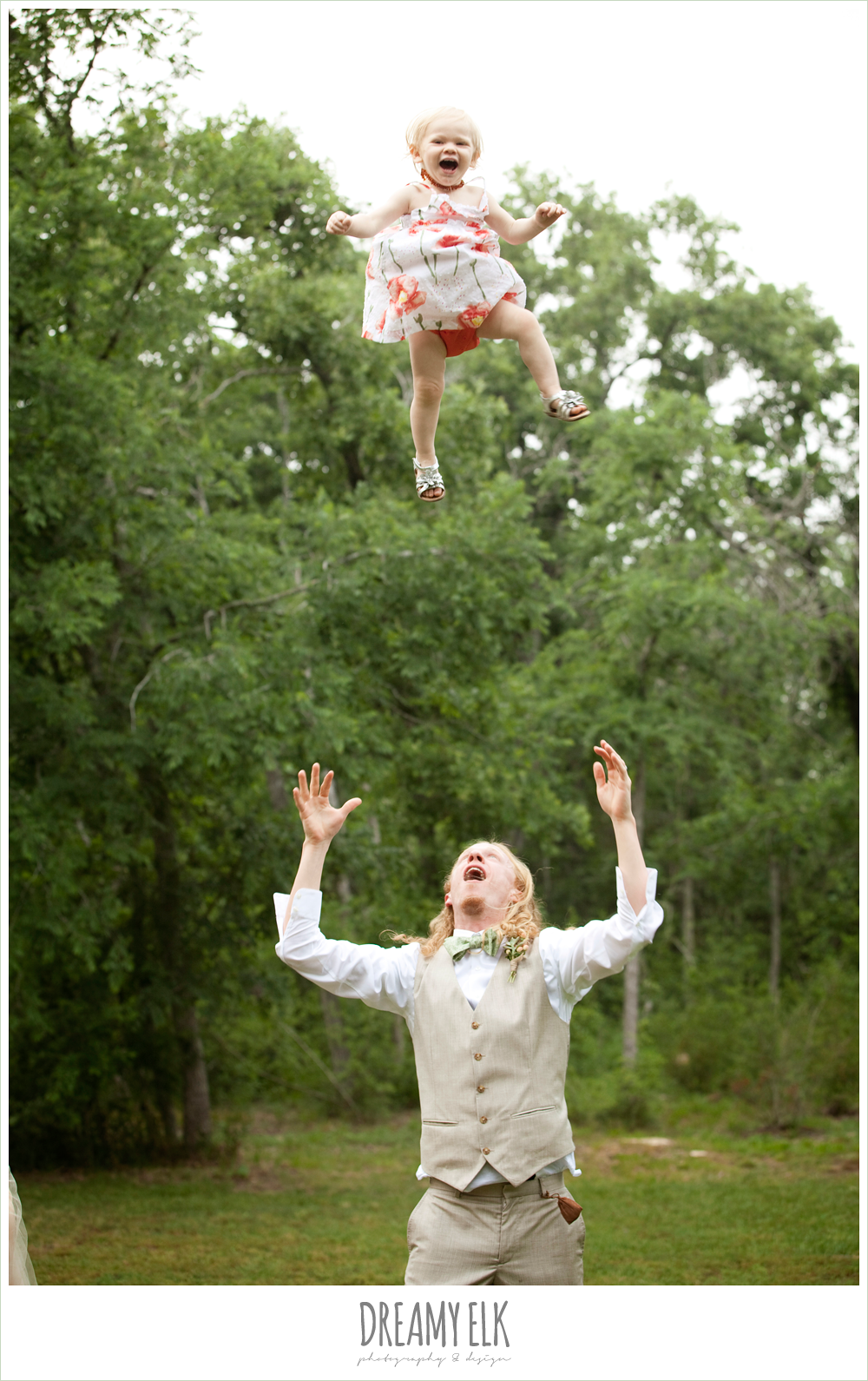 groom throwing daughter up in the air