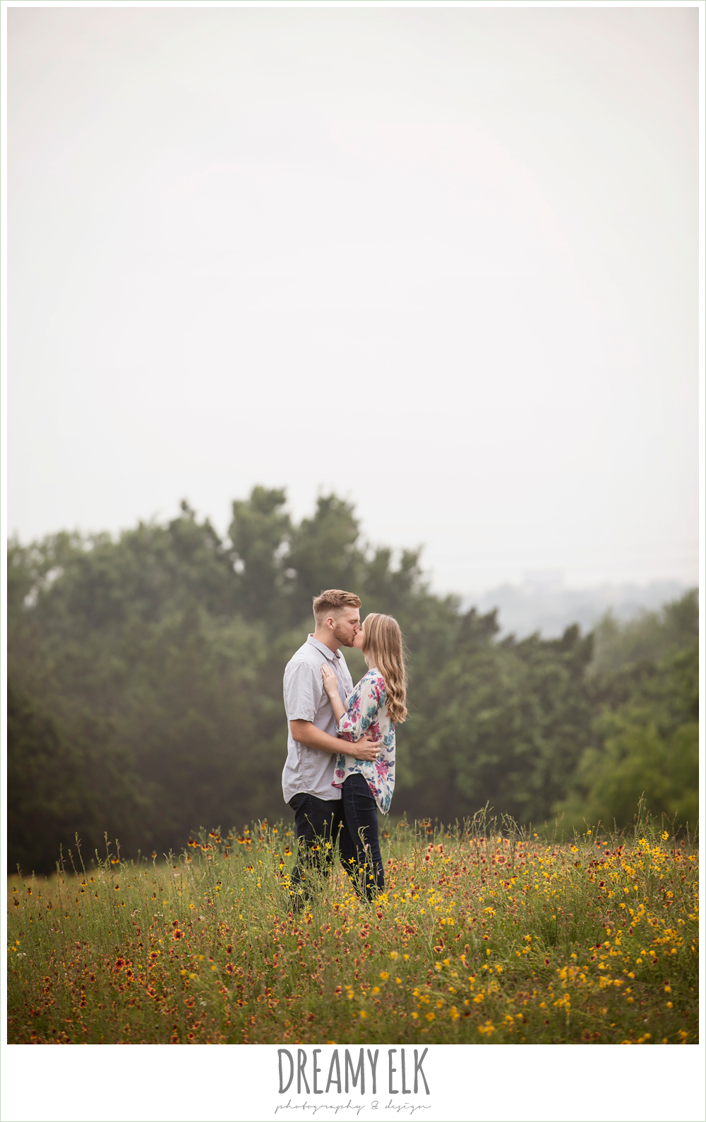couple kissing in a field of wild flowers, overcast engagement photo, walnut creek park, austin, texas {dreamy elk photography and design}