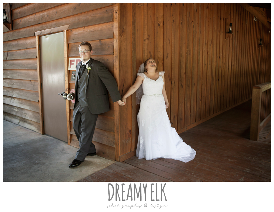 bride and groom holding hands around a door, amber springs summer wedding photo {dreamy elk photography and design}