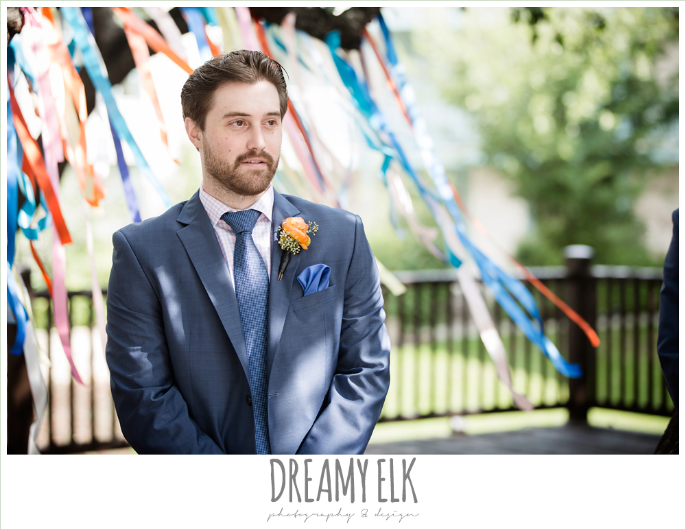colorful streamers in trees ceremony decorations, groom in men's wearhouse navy suit pink shirt and navy tie, groom's reaction to bride walking down the aisle, colorful outdoor sunday morning brunch wedding, hyatt hill country club, san antonio wedding photo {dreamy elk photography and design}