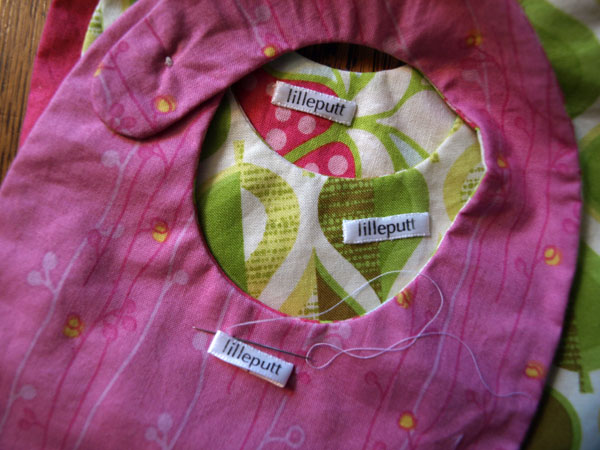 Sewing the last of the labels on the bibs… Note to self: Next time, sew the labels on FIRST.
