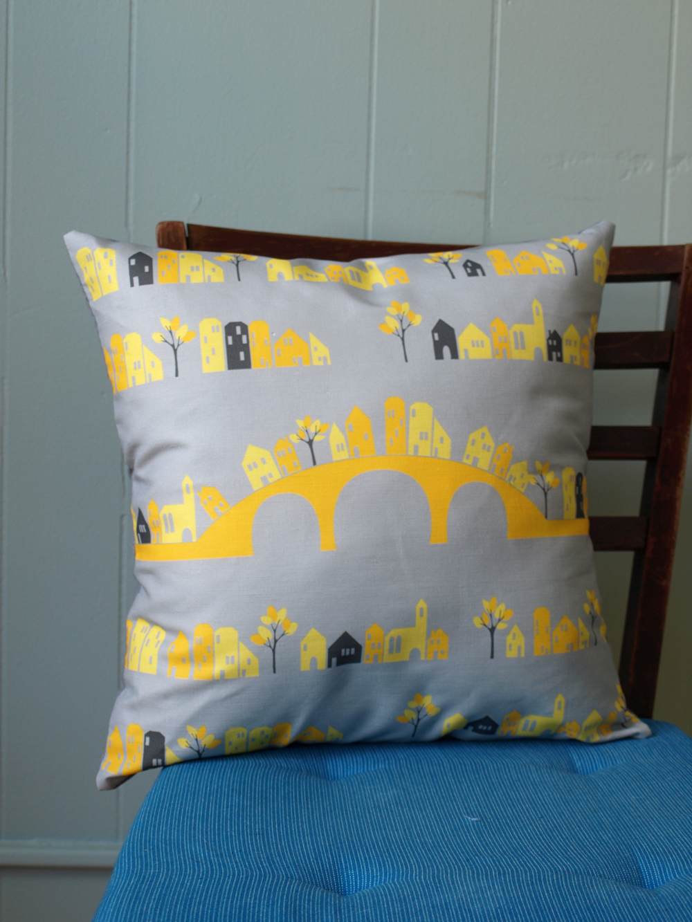 Grey and yellow house patterned pillow