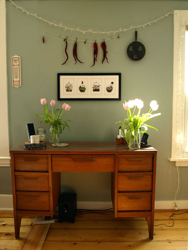 "The final placement of my lovely botanical prints from Quill & Fox, and one of my favorite nooks in our home. The desk I picked out for my boyfriend (with a matching bureau) back in Brooklyn, from an antique shop way down 5th Ave… around 17th Street I think; and other favorite items, our dollar ""Handyman Rents It!"" Portland thermometer (left), drying chili peppers (I'm amazed there are any left), the wooden trivet with heart cut outs, the pine wood floors… and Easter tulips!"