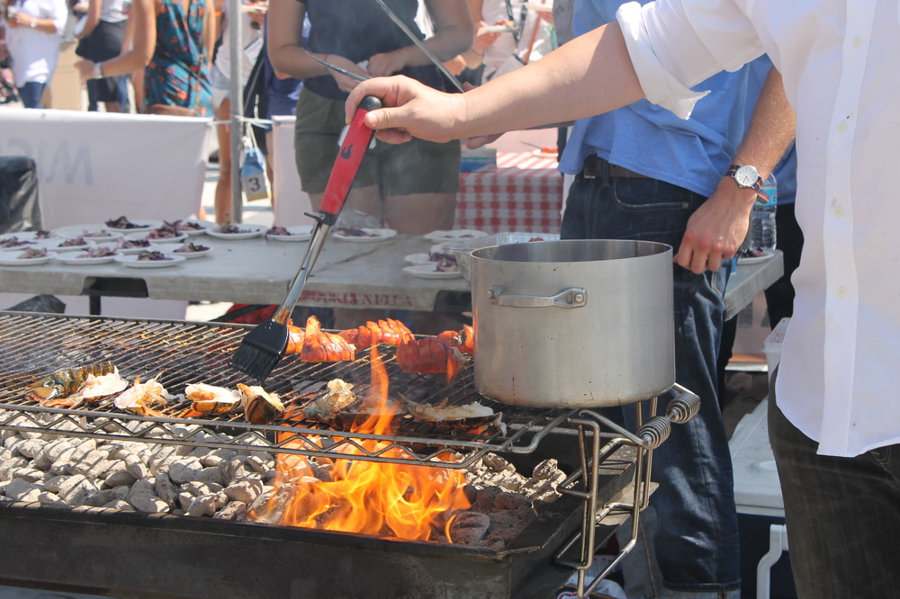 A grill master from Luke's Lobster butters lobster tails over open-flame.