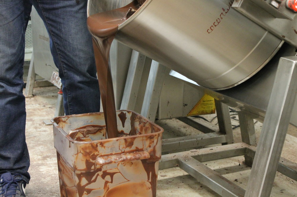 Chocolate being poured out of the grinding drums.
