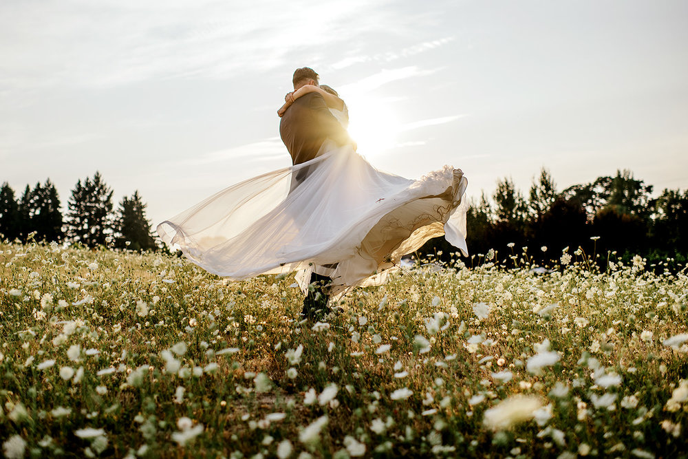Groom spinning bride in a white flower field
