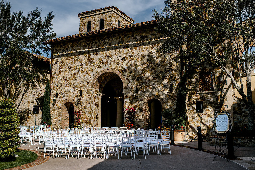 Italian Inspired wedding ceremony space with beautiful white chairs.