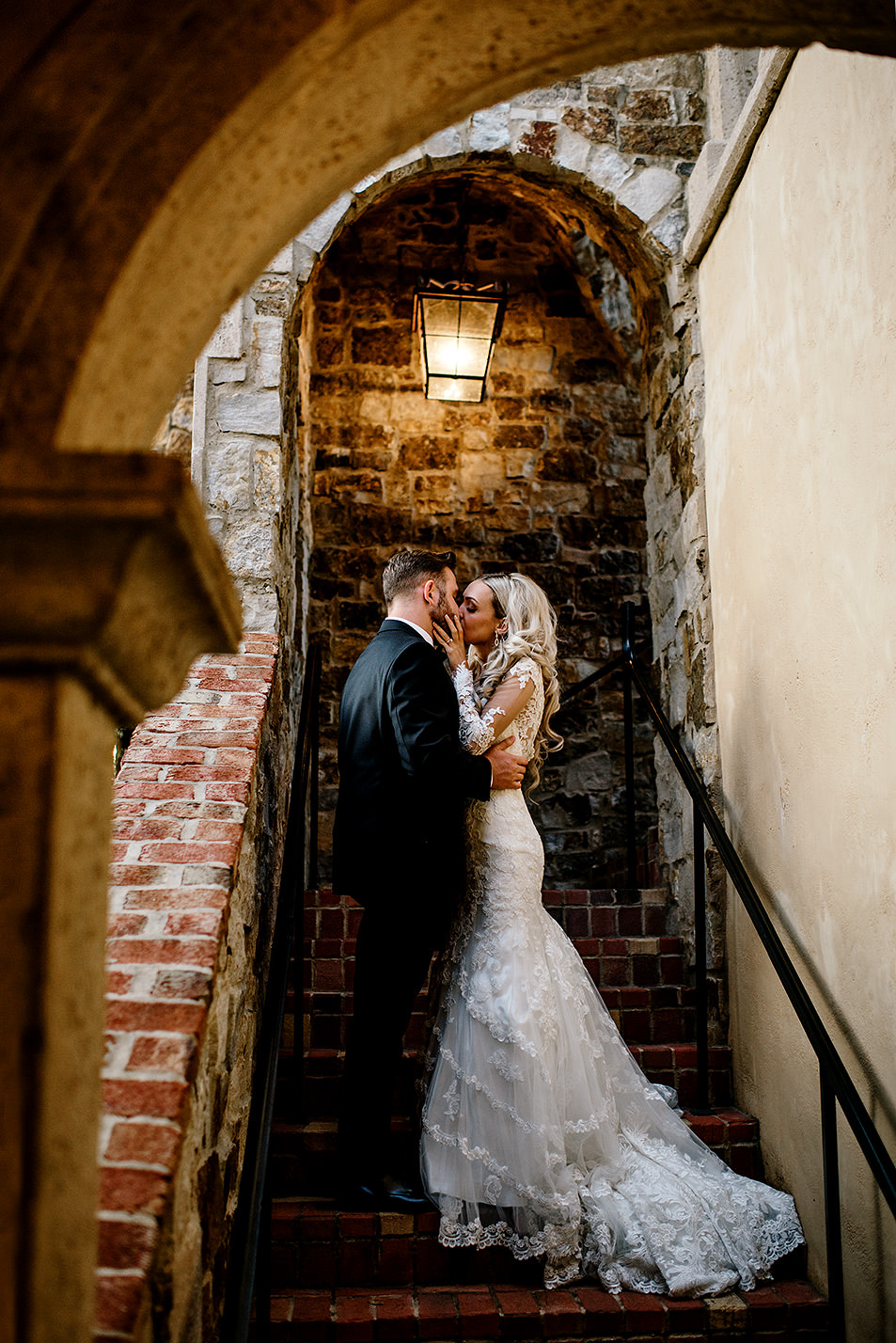 Portrait of a bride and groom kissing under a beautiful italian inspired stairwell at Bella Collina Florida.
