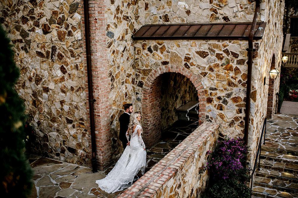 Bride and groom walking through the beautiful cobble stoned villa at Bella Collina Florida