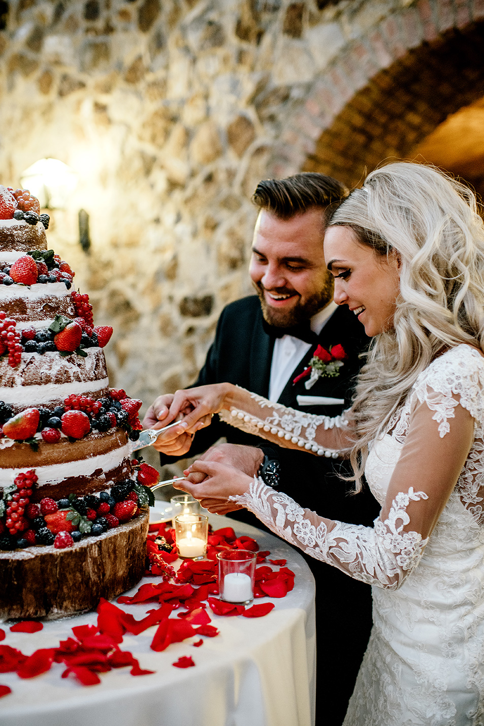 Bride and groom smiling while cutting their naked wedding cake at Bella Collina Florida