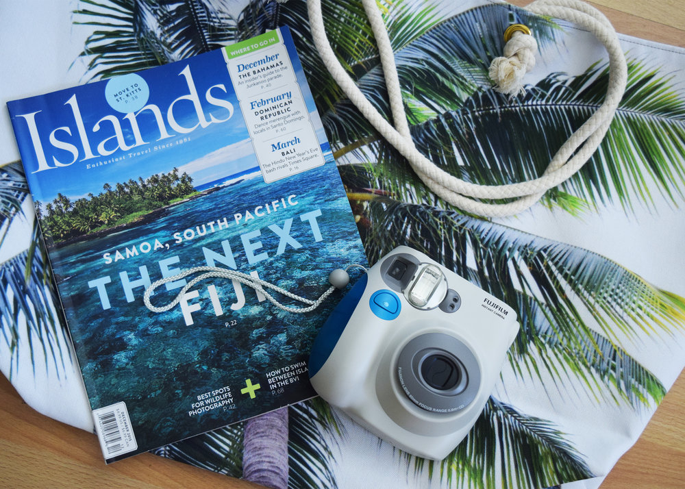 caribbean palm weekender tote with islands magazine and instax camera on floor.jpg