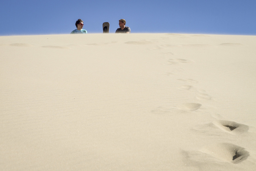 Sandboarding down classic Oregon sand dunes.