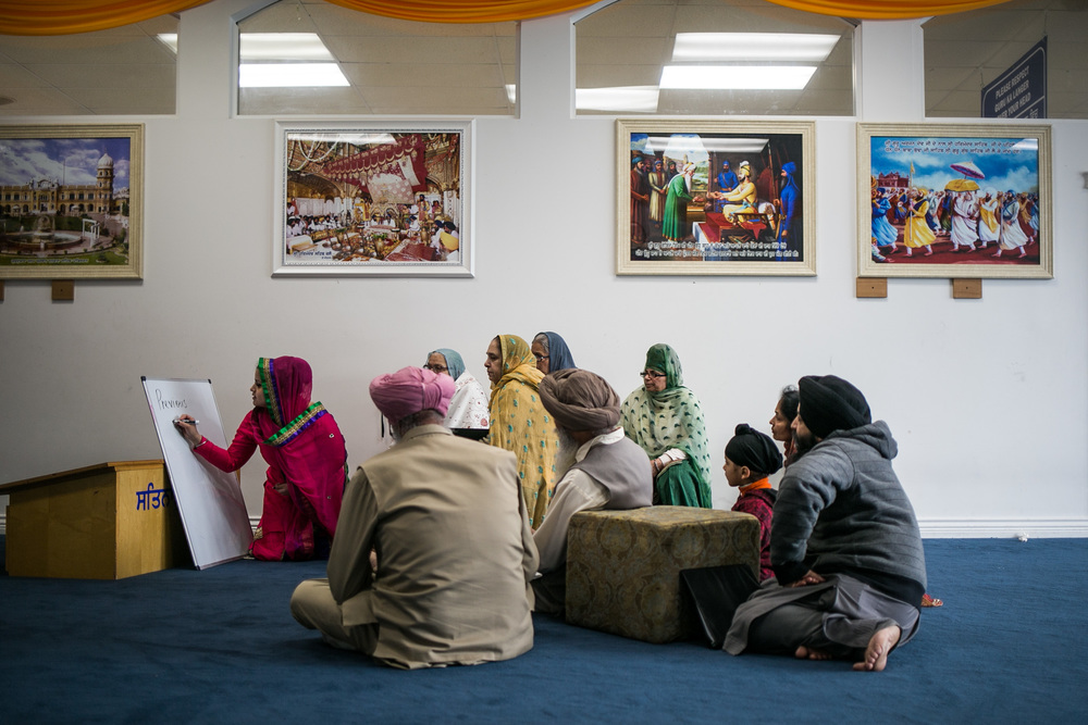 "Western Washington University student, Sukhmanii Kahlon, teaches the meaning of english words ""previous"" and ""sore"" to Sikh elders during her weekly class at Guru Nanak Gursikh Gurudwara following a prayer service on March 1, 2015. In her classes, Kahlon teaches words and phrases that are relevant to scenarios in the everyday lives of the Sikh elders such as visiting a doctor."