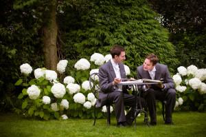 Groom and Bestman looking at wedding album