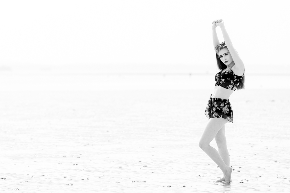 Hi-key girl in black and white on a beach
