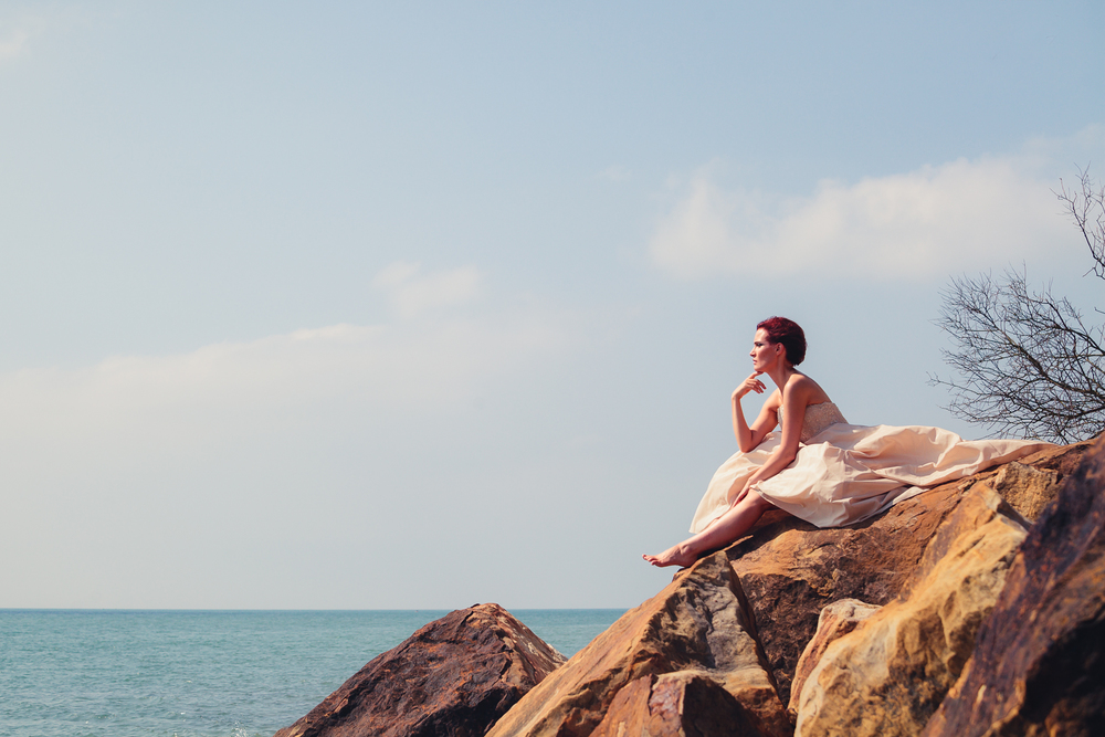 bride sitting on rocks