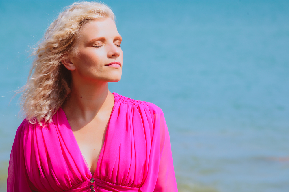 Blond woman in a pink dress with sun on her face