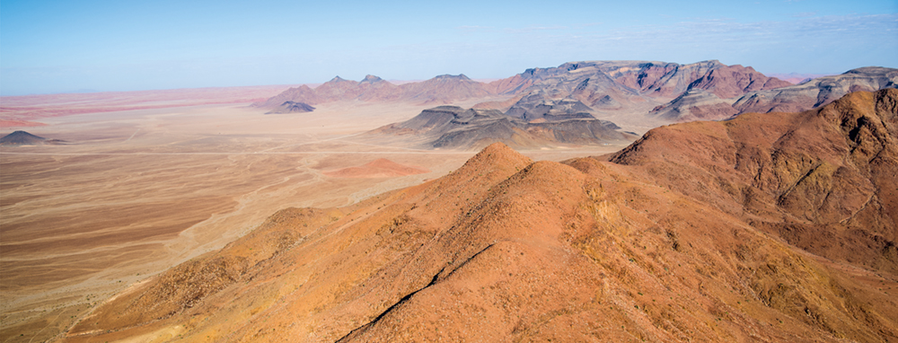 Wenn man sich Sossusvlei nähert, verwandelt sich die steinige Landschaft des Naukluft Gebirges in das sandige Meer des NamibRand Naturparks    in den Farben Gelb bis Rostrot   Photo © 2016 Jürgen Wettke. All rights reserved