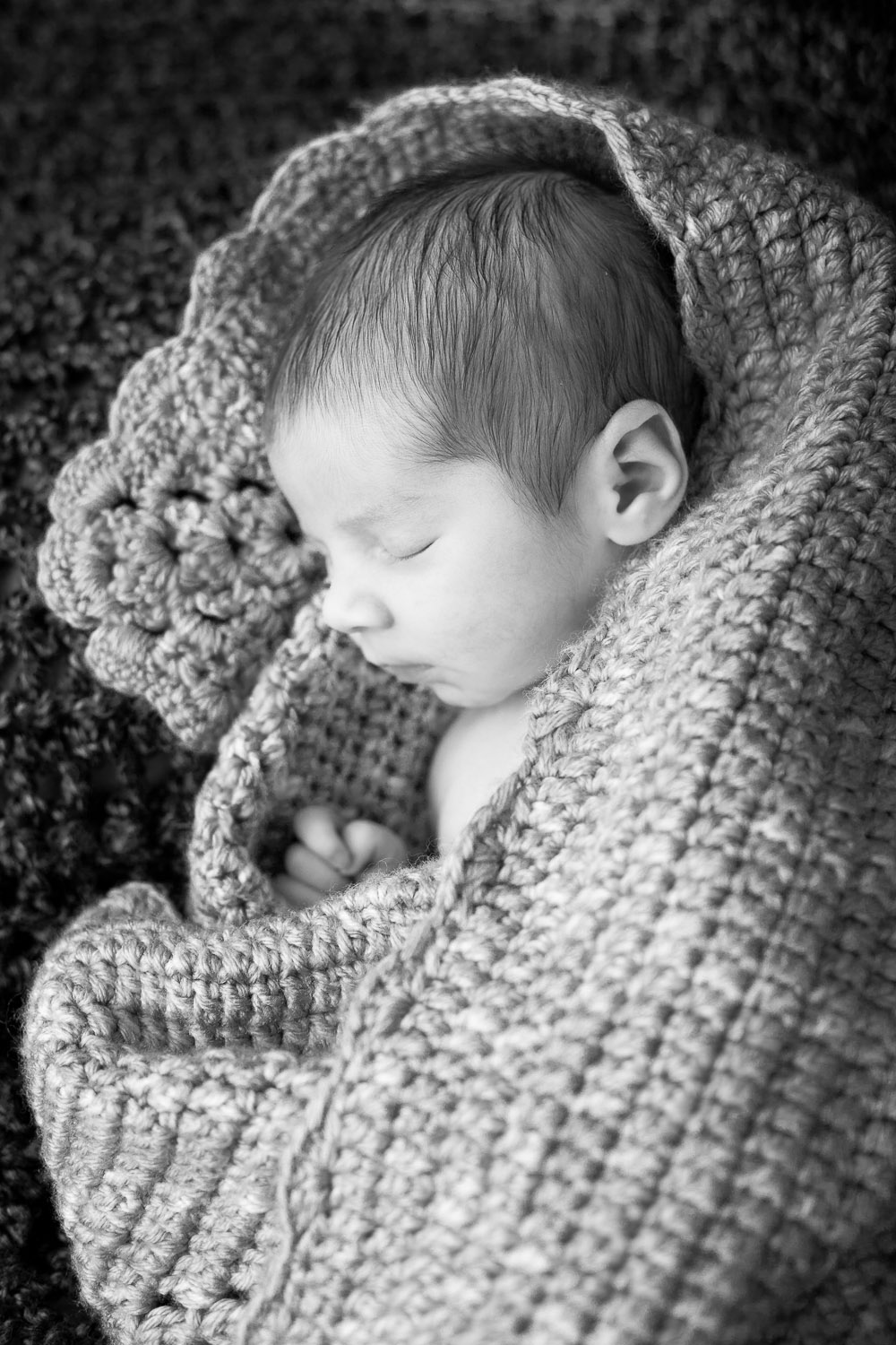 newborn baby sleeping in knit blanket