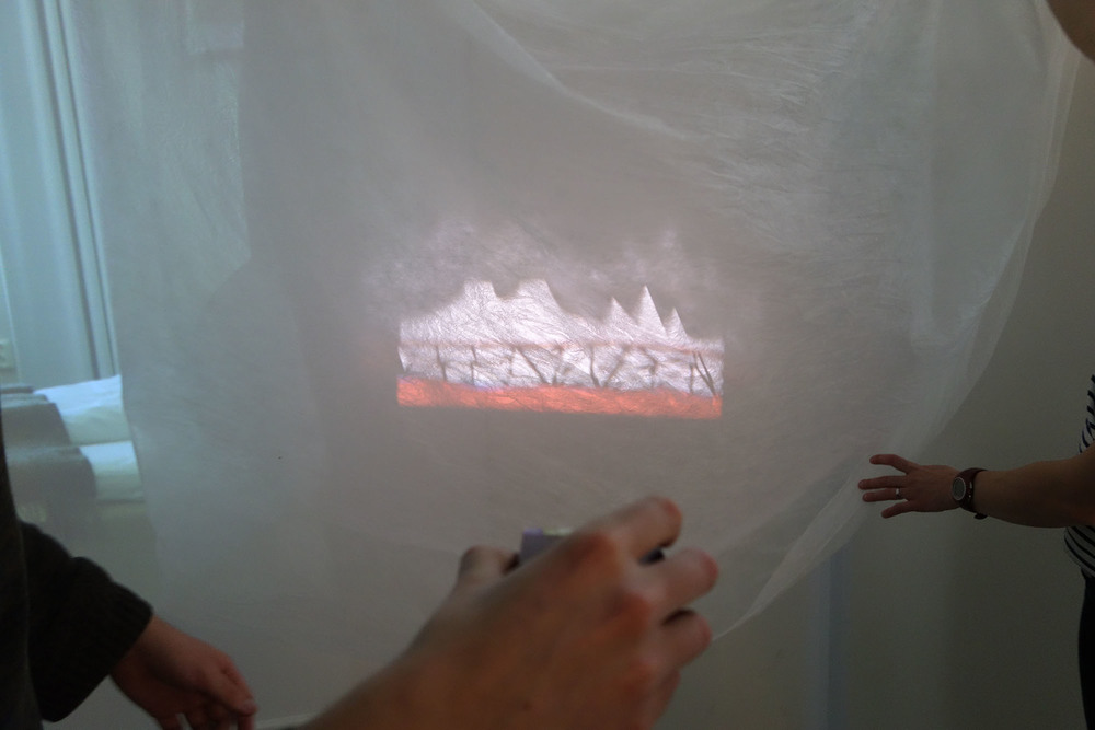The mini projector projecting on semi-transparent fabric