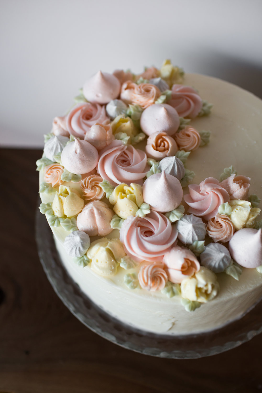 white cake w/ white buttercream, swiss buttercream flowers, and meringues.