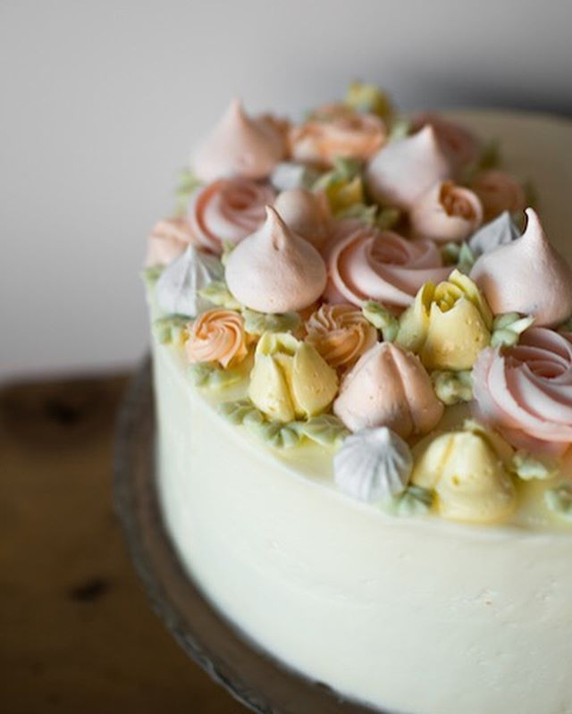 """Happy Thursday and our very own Cake Giveaway Day! Today we're featuring our classic White Cake with white buttercream, swiss buttercream flowers & meringues. Who would you share this with?! Tag them (in separate comments) for the chance to win a FREE 6"""" cake of your choice! Extra entry for sharing this post!!🎉 If you can't wait, head downtown to purchase a slice of this beauty, while supplies last! •giveaway ends at midnight•  #cakestagram #cakegiveaway #whitecake"""