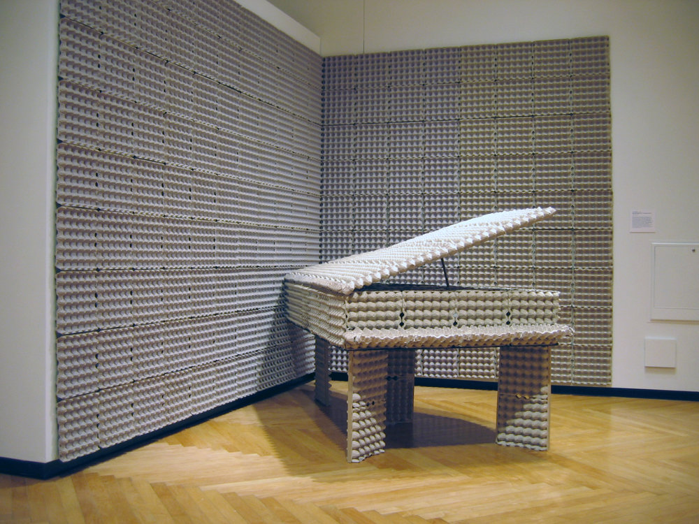 "'Egg Crate Grand: A Soundproof Piano' , 2004, 57 x 50 x 90(with top open). The grand piano-sized assemblage is constructed solely from egg crates found on the street by the Broken Egg restaurant in Ann Arbor near where the artist lived while teaching at the University of Michigan in 2003-04. Here the shape of the piano as an evocative sculptural form is referenced, in addition to the grassroots use of egg cartons as soundproofing in home recording studios of years past. It becomes a silent, highly absorbent, soundproof piano - the perfect instrument for a performance of John Cage's ""silent"" work 4'33""."