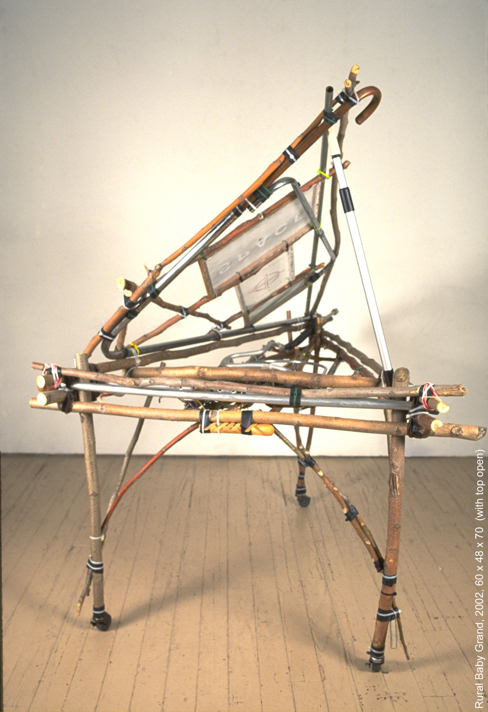 "'Rural Baby Grand' , 2002, 60 x 48 x 70 (with top open). Constructed humbly from branches, twigs, screens, a cane, a crutch, and bits of discarded electronics, in an ""Adirondack"" style, the piano exudes a transparent poetic folk art quality as it mixes ""high"" and ""low"" art forms. The triangular body refers more to the harpsichord than the modern grand with its sweeping wing lid and larger scale. Except for the hint of sound potential provided by a few tongue depressors as keys, the piano is silent."