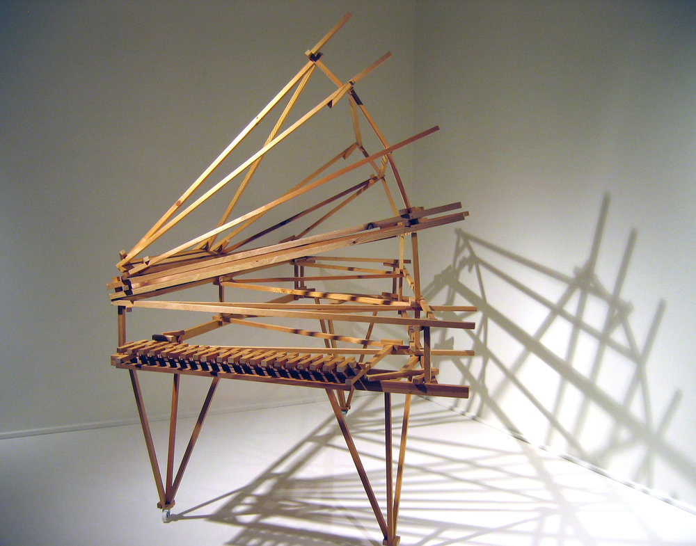 "'Zen Fan Grand' , 2006, 68 x 48 x 76(with top open). To create the simplest possible ""piano"" structure (with fanned top and removable legs), I cut wood strips into 2"", 4"". 6"", 8"", 1', 18"", 2', and 1/2 ft. increments up to 6' lengths. They were arranged in the most obvious manner to provide rigidity, with no additional cutting, using a hot-glue gun and brad stapler. The key configuration is the simplest method I could come up with using the pieces and rubber bands to make a playable (and removable) keyboard. The ""notes"" are essentially the same ""clink"", but have very subtle differences, especially when amplified. These sounds are the antithesis of a standard piano, and emphasize the percussive aspect of the instrument."