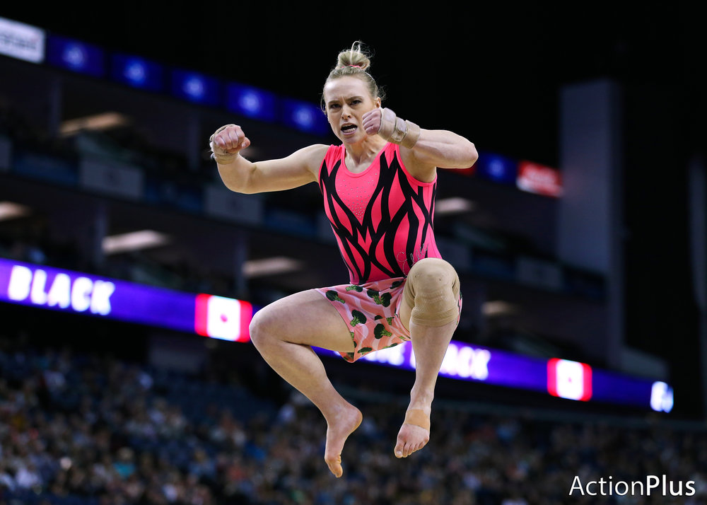 Ellie Black of Canada leaps into the air in celebration after performing on the floor while wearing shorts with a broccoli pattern.