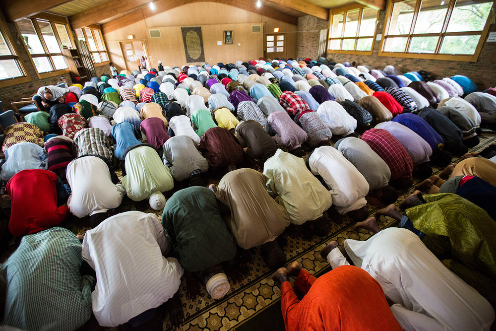 Men offer Sajdah, which means prostration to God in the direction of the Kaaba at Mecca during a congressional prayer on a recent Friday at the East Side Mosque of Madison. Photograph by Saiyna Bashir, July 2016, all rights reserved.