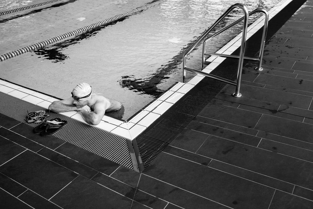 We are Triathlon   Das Training unterteilt sich in verschieden intensive Einheiten, die akribisch eingehalten werden. Beim Schwimmen kontrolliert Christian, während der kurzen Pausen, seine Notizen.